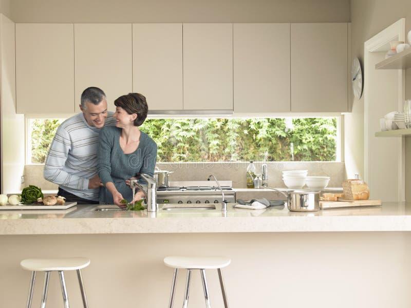 Légumes de lavage de femme tandis qu'homme l'étreignant par derrière dans Ki image stock