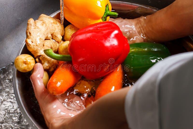 Légumes de lavage de mains dans l'eau photographie stock