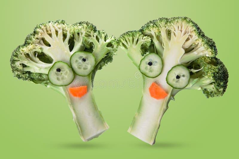 Légumes drôles créatifs Brocoli et concombre sur un fond vert clair photographie stock libre de droits