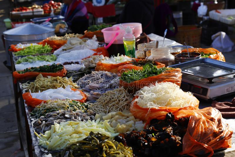 Légumes et d'autres produits dans une stalle du marché de Shaxi, Yunnan, Chine photos stock