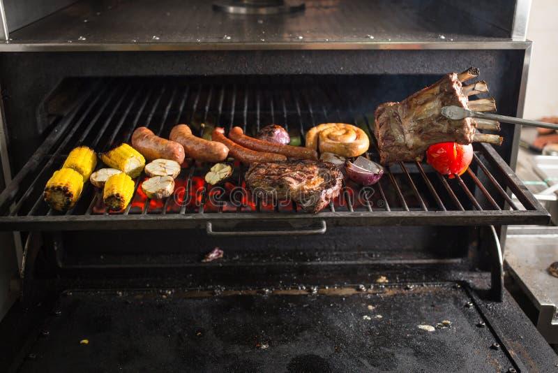Légumes et viande sur le gril sur les charbons chauds avec de la fumée photo libre de droits
