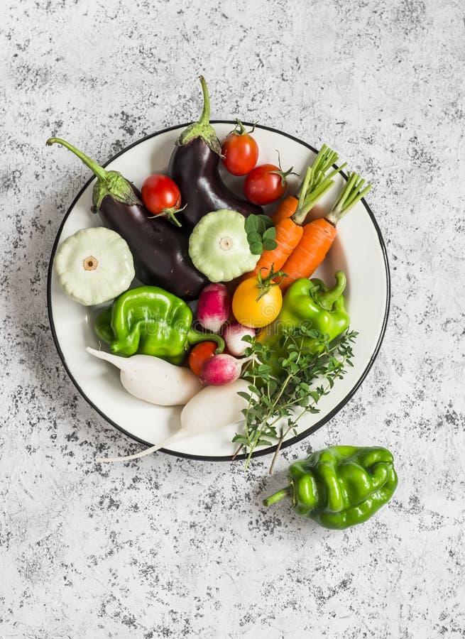 Légumes frais - aubergine, radis, paprika, tomates, thym, origan dans une cuvette d'émail sur un fond clair photo stock