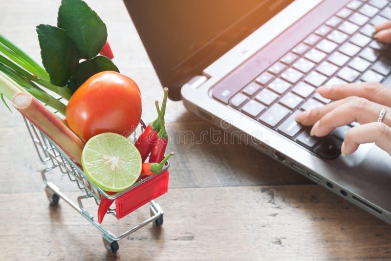 Légumes frais dans le caddie avec la femme à l'aide de l'ordinateur, Onl photos stock