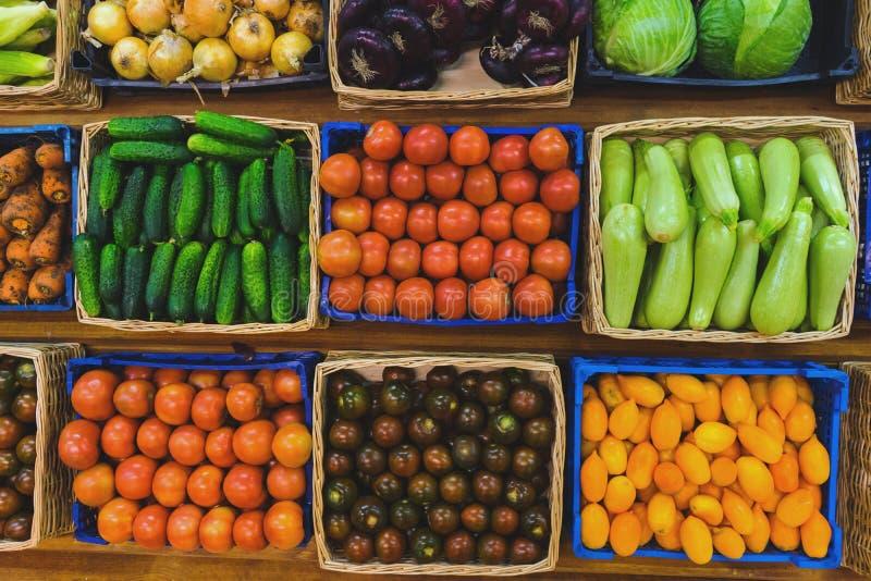 Légumes frais dans les paniers en osier sur le compteur d'un petit marché végétal images stock