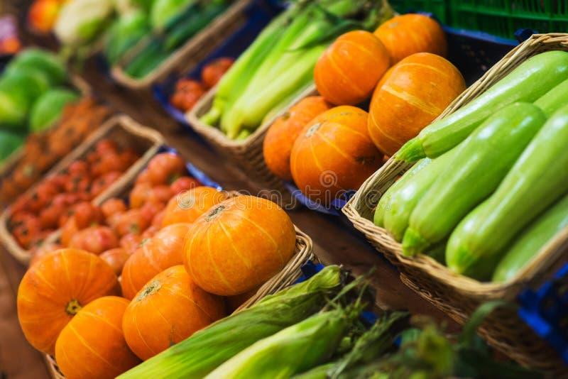 Légumes frais dans les paniers en osier sur le compteur d'un petit marché végétal photo libre de droits