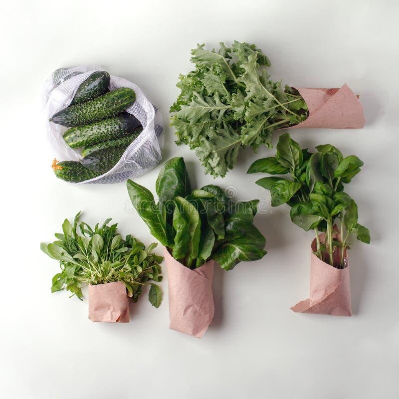 Légumes frais dans les sacs de coton d'eco, paquet de papier sur la table dans la cuisine Concombres, salade, chou frisé, basilic image libre de droits