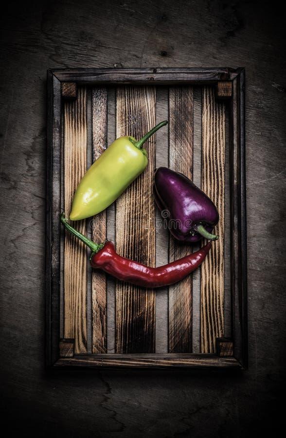 Légumes frais dans une boîte rustique brûlée de texture pour le fond Conseil en bois superficiel par les agents approximatif tone photos stock