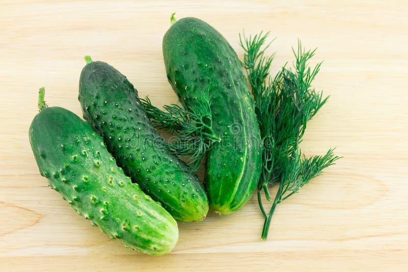 Légumes frais du concombre trois avec un brin d'aneth sur un plan rapproché en bois beige léger de fond d'un régime léger de cass images stock