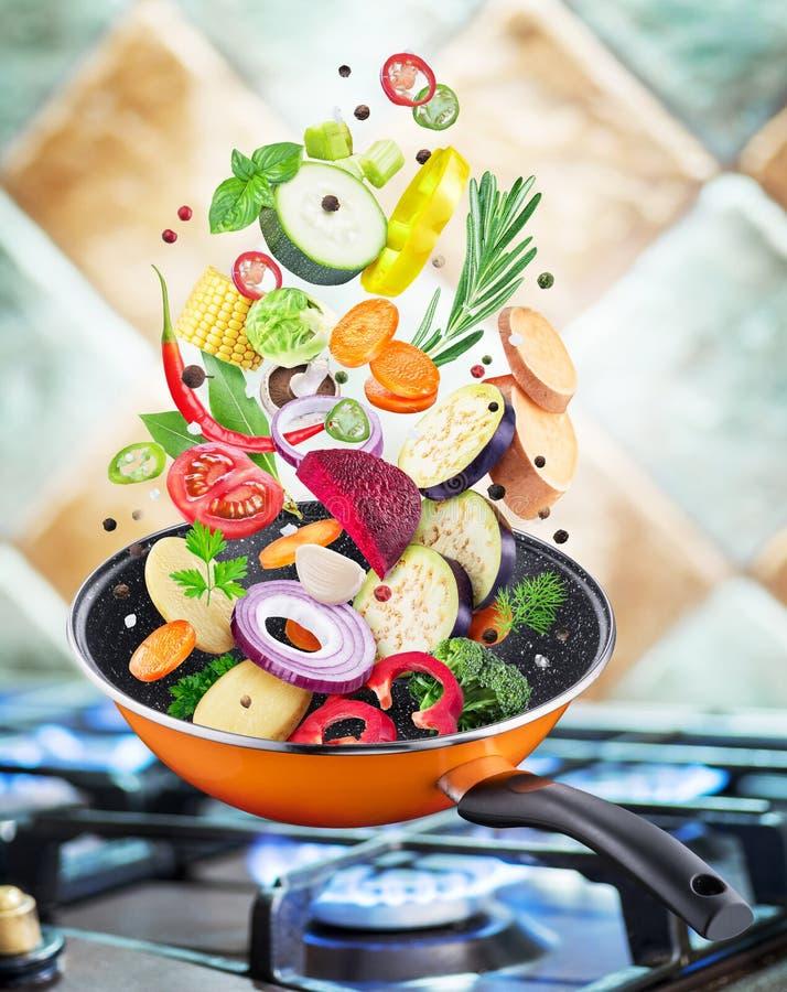 Légumes frais et épices volants tombant dans une casserole image stock