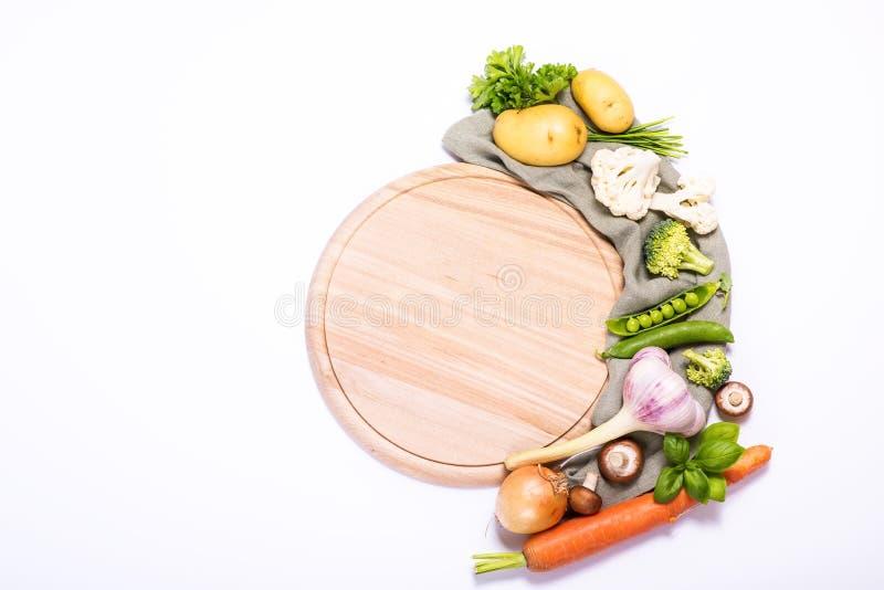 Légumes frais pour faire cuire autour de la planche à découper vide ronde, ingrédients pour la consommation saine, fond blanc de  image stock