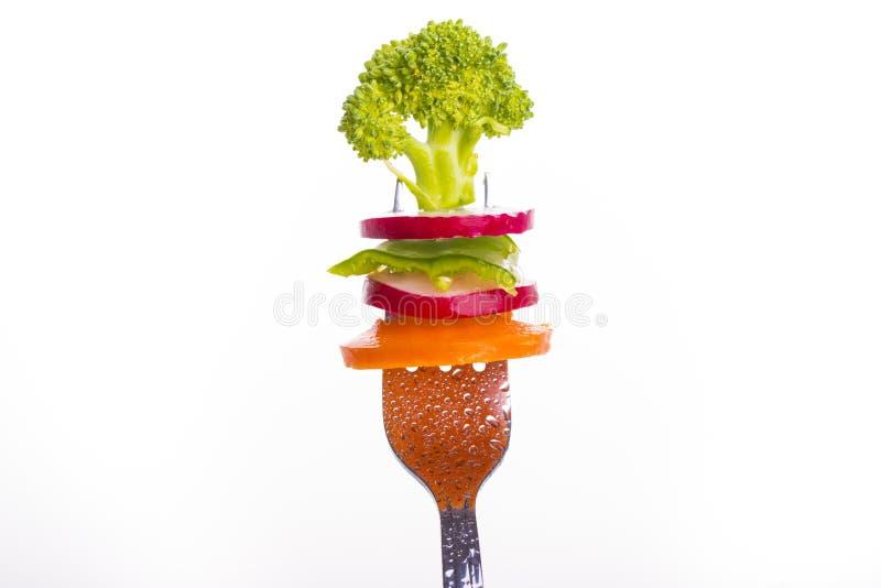 Légumes frais sur une fourchette d'isolement sur le fond blanc image libre de droits