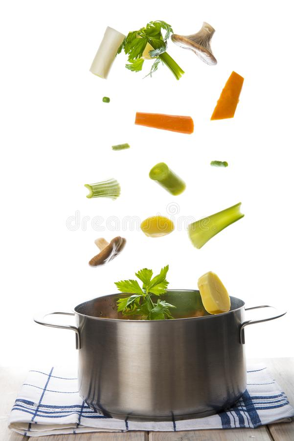 Légumes frais tombant dans un pot d'isolement sur un backgrou blanc photo stock