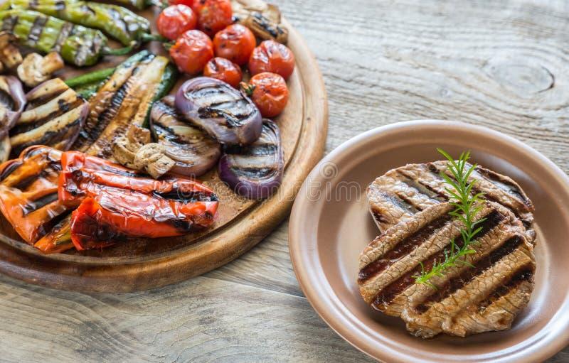 Légumes grillés avec des biftecks de boeuf sur le conseil en bois images stock