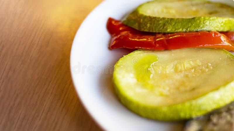 Légumes grillés, paprika doux rouge et courgette du plat blanc sur la table en bois dans le restaurant Foyer s?lectif image stock