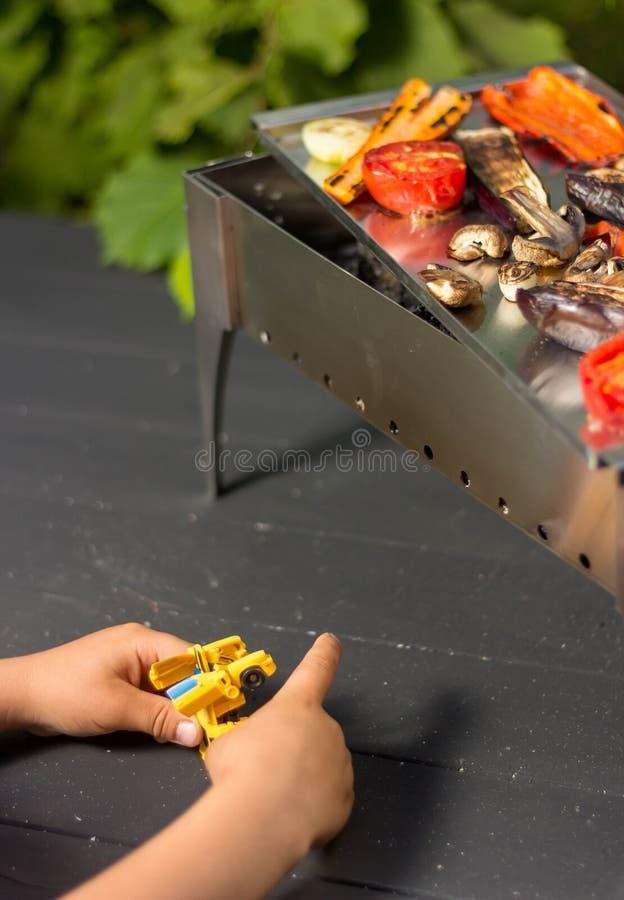 Légumes grillés sur le barbecue et le garçon de jouer images libres de droits