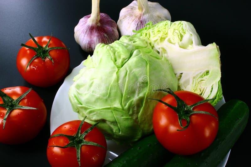 Légumes juteux et frais dans le plat rond blanc sur le fond noir photographie stock libre de droits