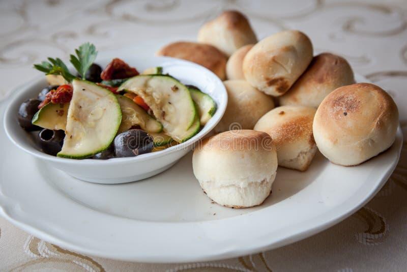 Légumes marinés : olives, courgette, tomates avec des petits pains de levure photos libres de droits