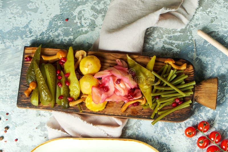 Légumes marinés sur un conseil en bois Beaux plats de portion Fond gris-clair Le d?ner de mariage avec de la viande de roulis a f photographie stock