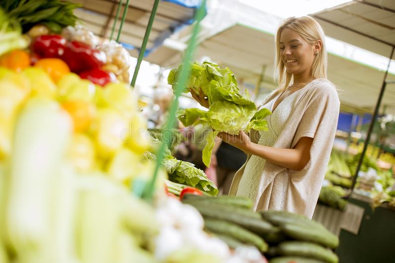 Légumes mignons d'achats de jeune femme au marché photos libres de droits