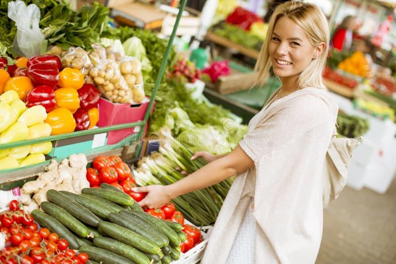 Légumes mignons d'achats de jeune femme au marché photos stock