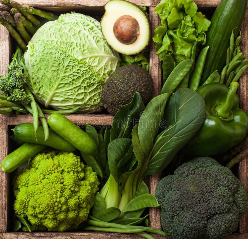 Légumes organiques crus modifiés la tonalité verts assortis dans la boîte en bois sur le fond foncé Avocat, chou, chou-fleur et c images stock