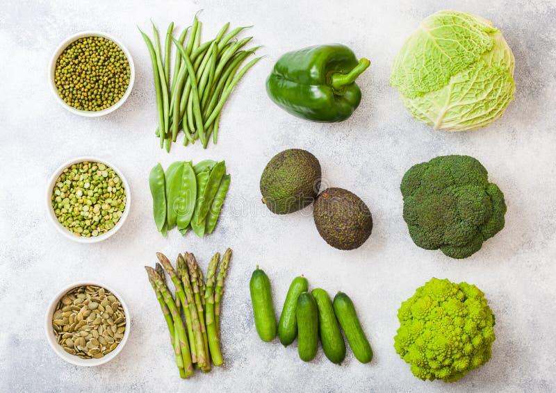 Légumes organiques crus modifiés la tonalité verts assortis sur le fond blanc Avocat, chou, brocoli, chou-fleur et concombre avec images stock