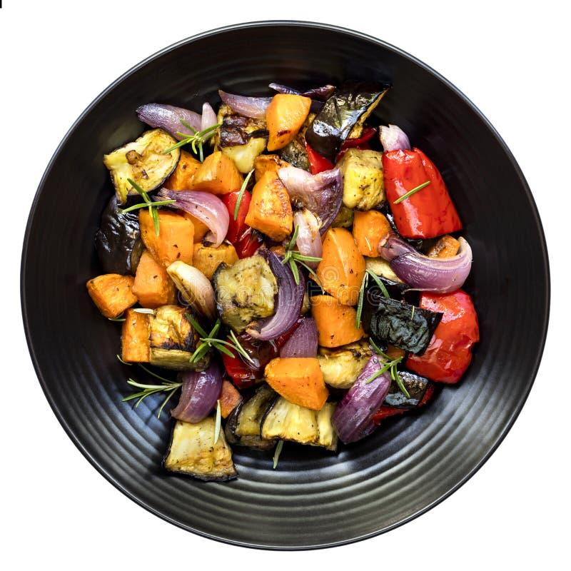 Légumes rôtis sur la vue supérieure de plateau noir d'isolement photographie stock