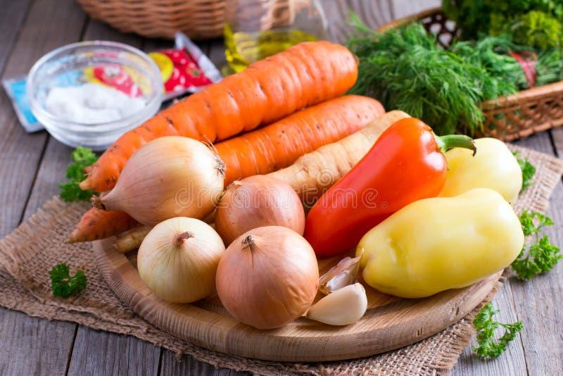 Légumes sur un panneau de découpage Oignons, carottes, panais, poivrons, ail photographie stock libre de droits