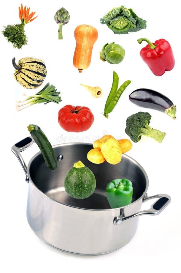 Légumes tombant dans un four néerlandais sur un fond blanc image stock