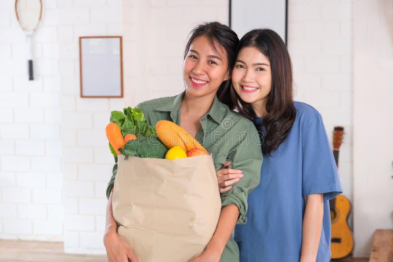 Lésbica asiática feliz dos pares que guarda o saco vegetal que looing na câmera após a compra na mercearia em casa Conceito do es foto de stock royalty free