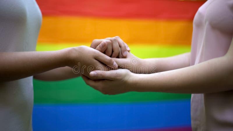 Lésbica que guardam as mãos, a bandeira do arco-íris no fundo, os direitos do lgbt e a unidade imagens de stock royalty free