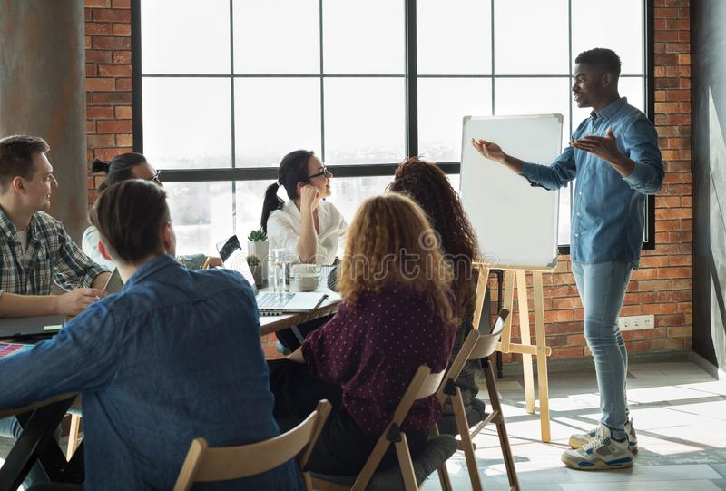 Líder afroamericano que da una conferencia a sus empleados en oficina fotografía de archivo libre de regalías