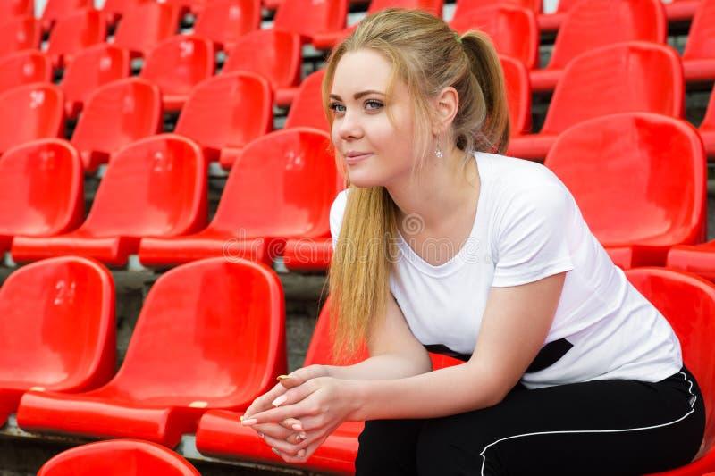 Líder da claque bonito da mulher que senta-se no pódio do estádio foto de stock