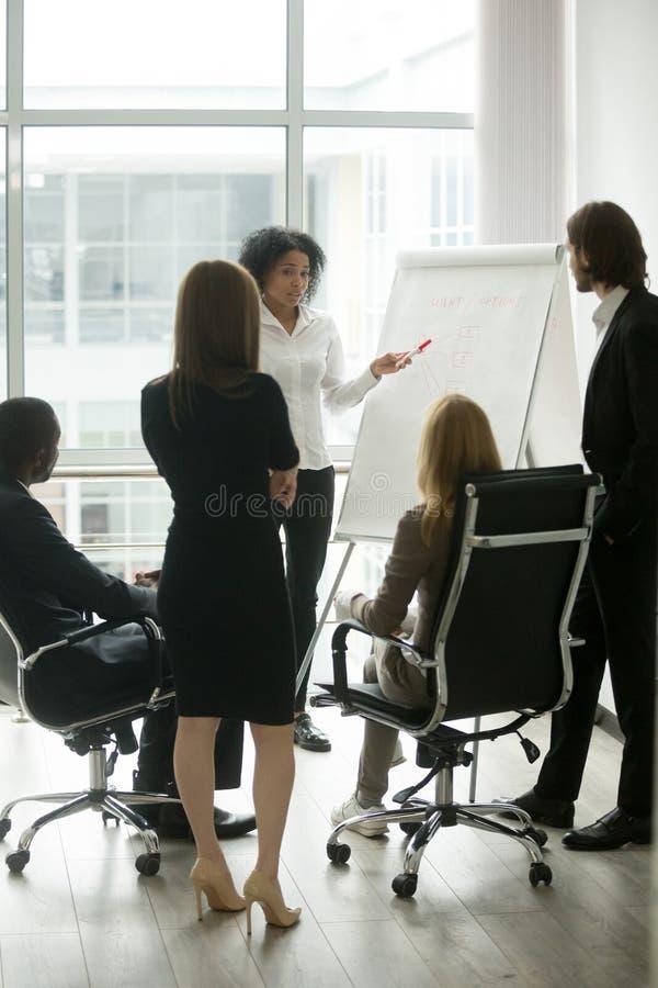 Líder da equipa preto que ensina executivos diversos na reunião do grupo fotos de stock