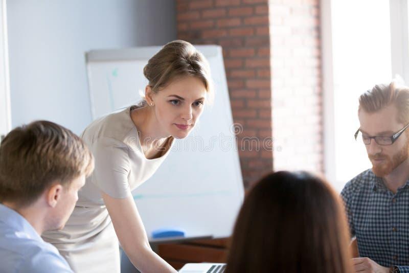 Líder da equipa sério da mulher que escuta ideias no clique do grupo imagem de stock royalty free