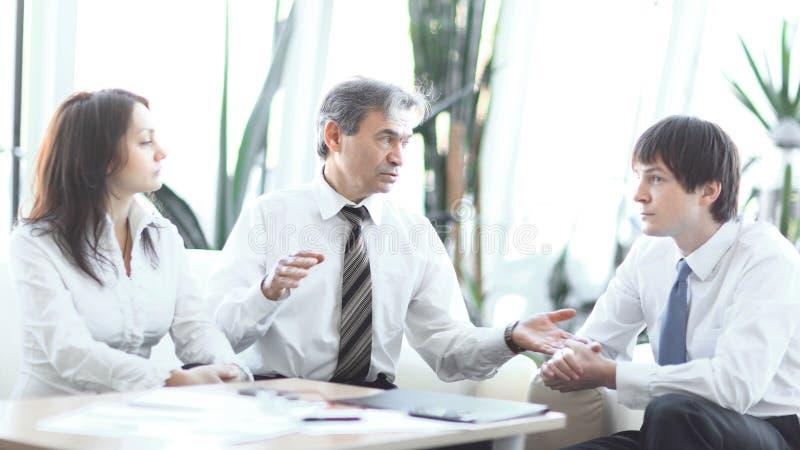 Líder de proyecto que habla con el equipo del negocio en el lugar de trabajo fotografía de archivo libre de regalías