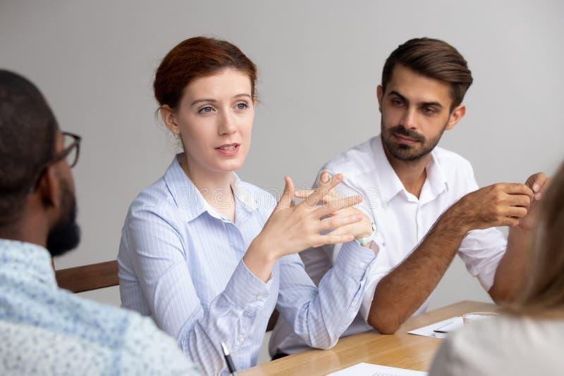 Líder de sexo femenino confiado hablar en el entrenamiento del grupo para explicar estrategia corporativa fotografía de archivo