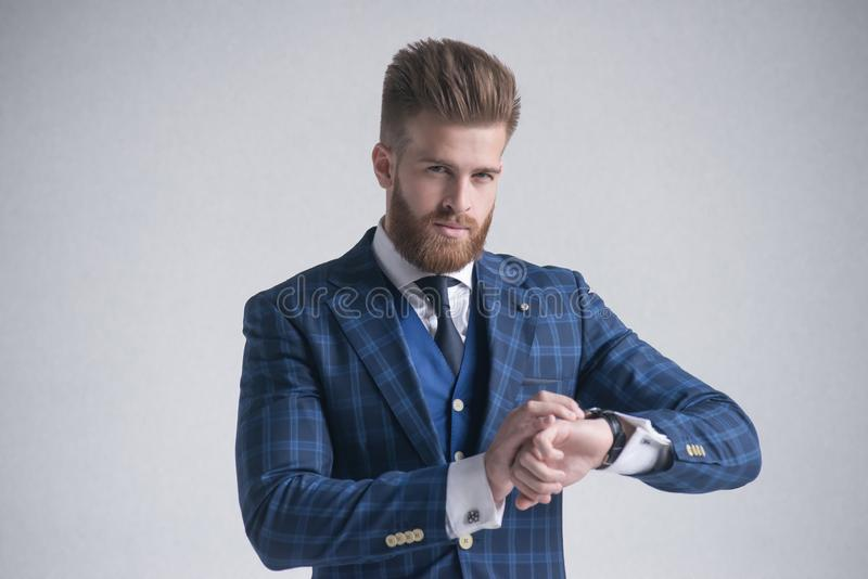 Líder elegante barbudo joven del hombre de negocios dentro vestido en el traje de tres piezas que comprueba el tiempo en su reloj fotografía de archivo