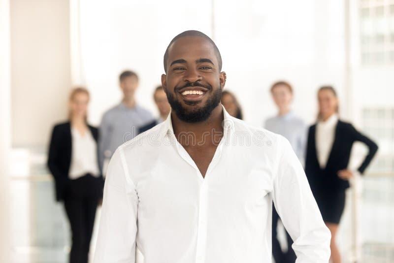 Líder incorporado do treinador africano feliz do negócio que levanta com equipe diversa fotos de stock royalty free