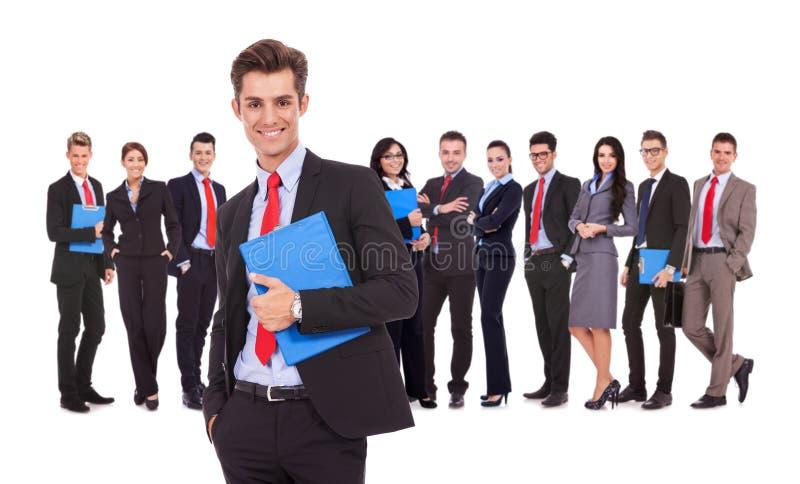 Líder que guardara uma prancheta com equipe do negócio atrás fotos de stock royalty free