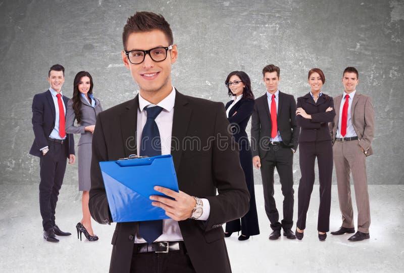 Líder que guardara uma prancheta com equipe do negócio atrás fotografia de stock