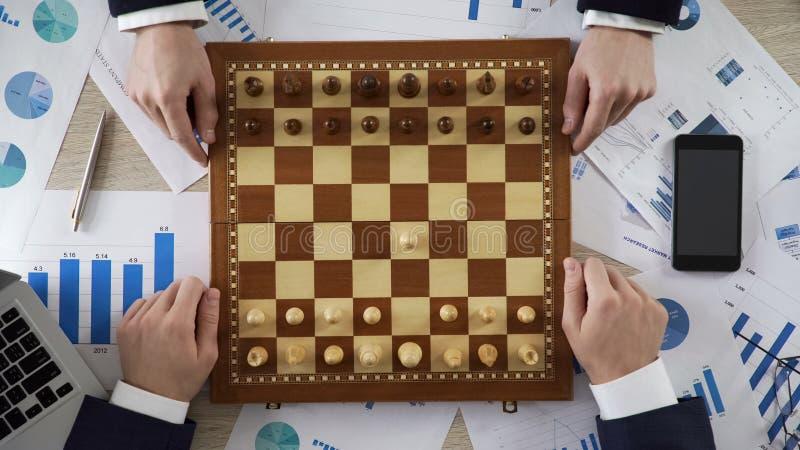 Líderes de la compañía que juegan a ajedrez, usando estrategia empresarial para ganar el mercado, visión superior imágenes de archivo libres de regalías