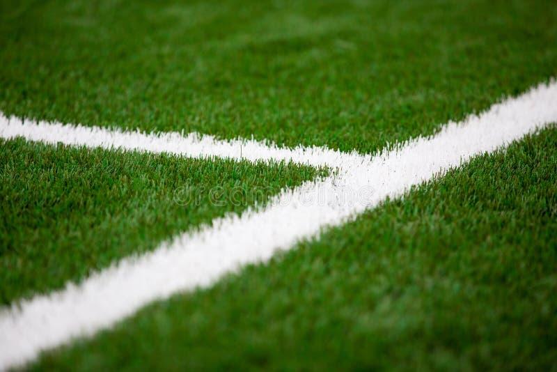 Línea blanca en un fútbol, hierba del artificil del campo de fútbol imagen de archivo