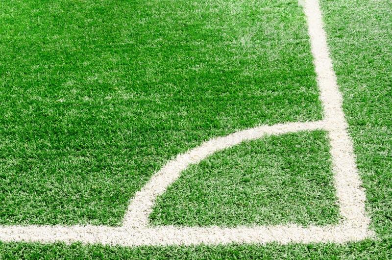 Línea de campo de la esquina blanca en la hierba verde artificial del campo de fútbol foto de archivo