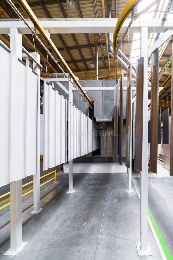 Línea de capa del polvo Los paneles del metal se suspenden en una línea de arriba del transportador fotografía de archivo