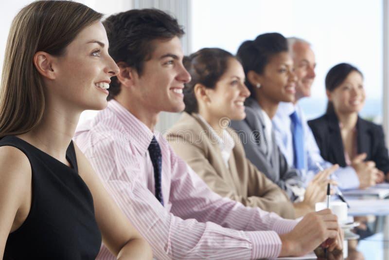 Línea de hombres de negocios que escuchan la presentación asentada en la tabla de cristal de la sala de reunión fotos de archivo