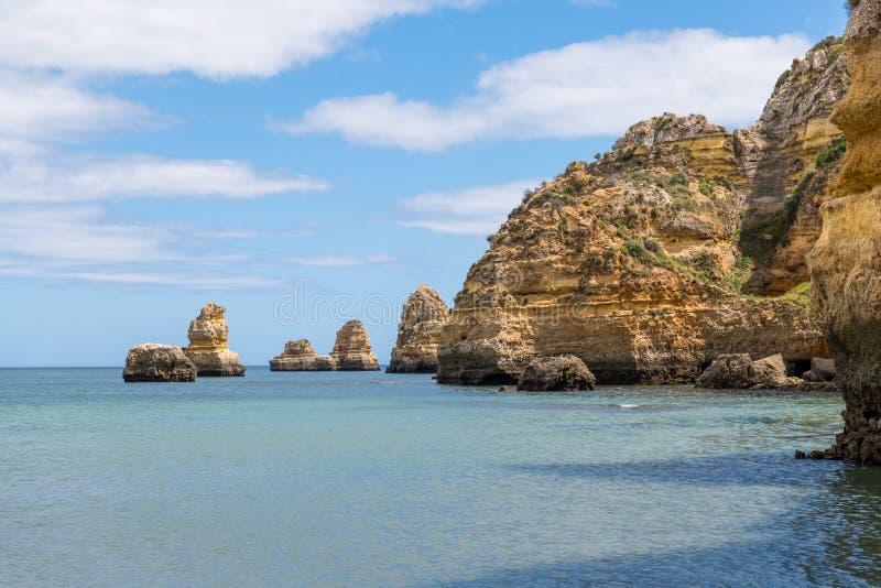 Línea de la playa de acantilados, de las formaciones de roca, del cielo azul, y de las aguas azules de la aguamarina tranquila imagen de archivo libre de regalías