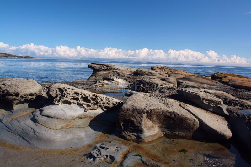 Línea de la playa rocosa que espera la tormenta imagenes de archivo
