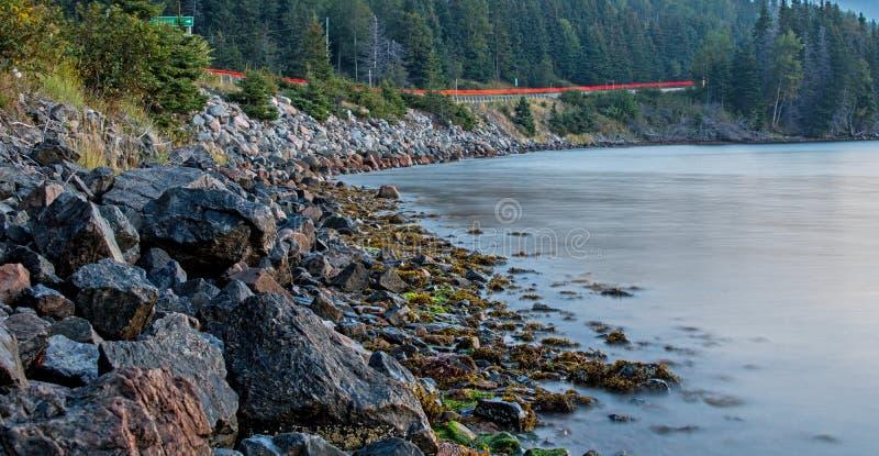 Línea de la playa y carretera en la iluminación del Pre-amanecer fotos de archivo