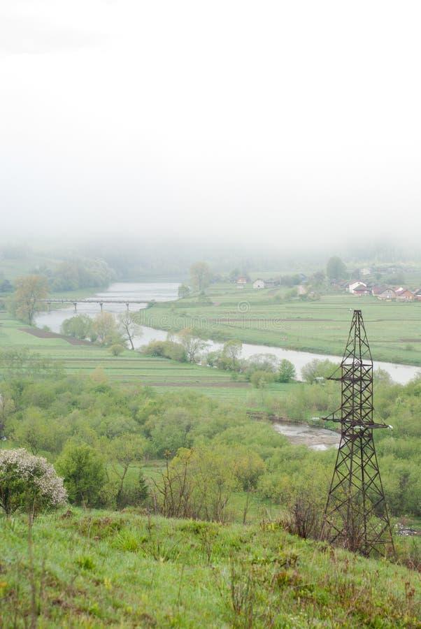 Línea de la transmisión tower Nube gigante Puente sobre el río Tiempo brumoso Cárpatos, Ucrania foto de archivo libre de regalías